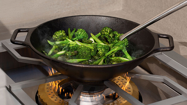 Vegetables being wok-cooked atop of a DCS Power Burner