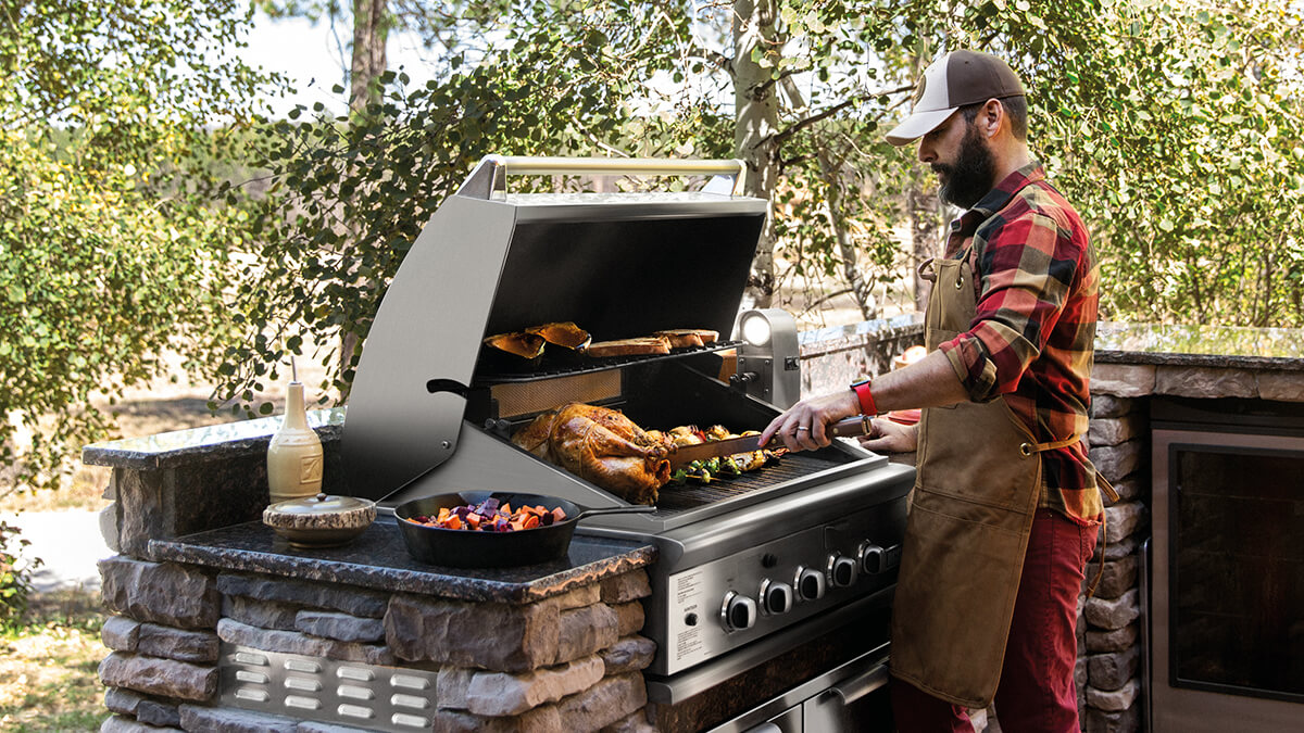 David Stanley cooking in a DCS grill with rotisserie at his outdoor kitchen in Colorado