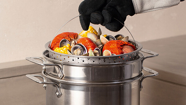 Hand wearing heat resistant glove, holding a steaming basket with boiled seafood