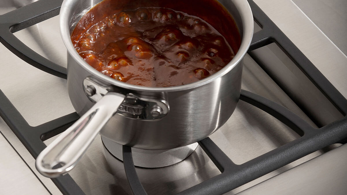 Stainless steel saucepan atop of DCS Sideburner
